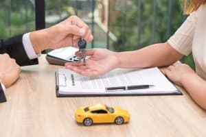 Businessman giving car key over car loan application document